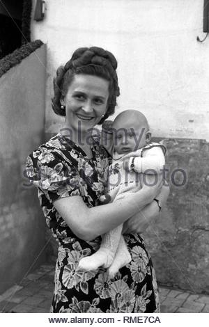 A woman holds a baby on the arm in Merseburg in the federal state Saxony-Anhalt in the area of the former GDR, German democratic republic. Foto: Siegfried Bonitz - Stock Photo