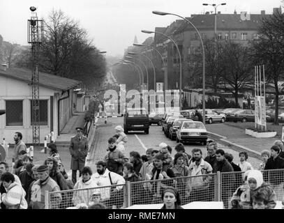 Numerous East Berliners stand in line at a border checkpoint to visit West Berlin after the fall of the Berlin Wall. - Stock Photo