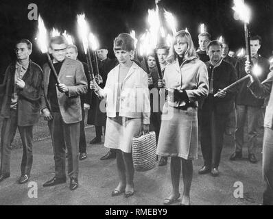 Teenagers march through the city center in a protest march with burning torches to a ceremony at the Platz der Opfer des Nationalsozialismus. - Stock Photo
