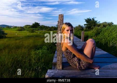 Attractive young woman in nature in sunset evening time sitting inclined on wooden post barefeet barefoot - Stock Photo