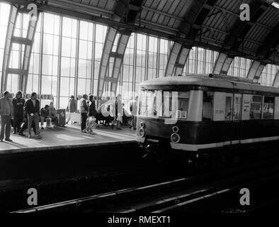 Waiting passengers at the S-Bahn station Alexanderplatz in East Berlin. - Stock Photo