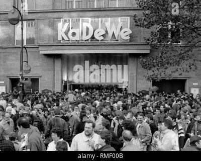 After the fall of the Berlin Wall, numerous East Berliners visit West Berlin. Here, view of  the crowd in front of the Kaufhaus des Westens at Wittenbergplatz. - Stock Photo