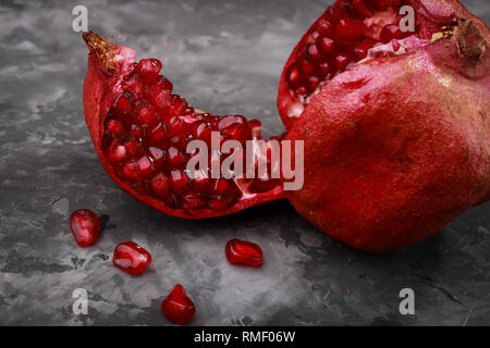 juicy ripe pieces of pomegranate on a dark background - Stock Photo