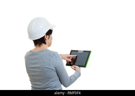 Rear view of young woman engineer wearing protective helmet using a tablet computer gadget to calculate looking up isolated over white background with - Stock Photo