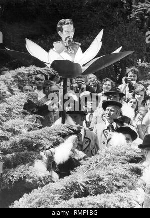 This photograph shows an event of the Koenig-Ludwig-Treuen on the 90th anniversary of the death of the king. They carry a staff with the portrait of King Ludwig II in a bloom through the street. - Stock Photo