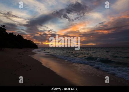 Twilight evening sunset. Waves, surf, swash at empty beautiful sandy beach on Foa island, Haapai islands or Ha'apai group, Tonga, Oceania, South Pacif - Stock Photo