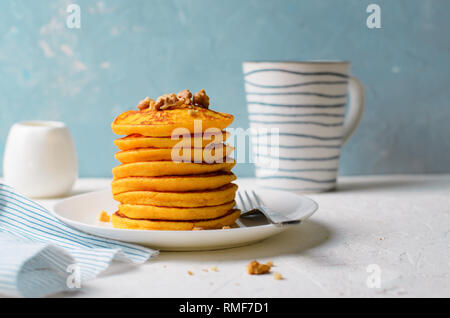 Pumpkin or Carrot Pancakes with Nuts, Stack of Homemade Pancakes on Bright Background - Stock Photo