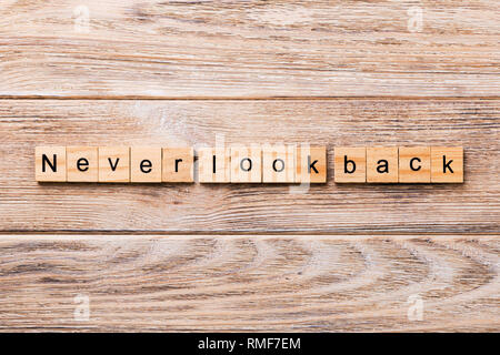 never look back word written on wood block. never look back text on wooden table for your desing, concept. - Stock Photo