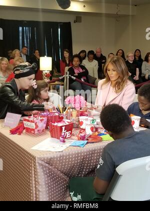 BETHESDA, MD FEBRUARY 14: Dressed in all pink, first lady Melania Trump brought ValentineÕs Day cards to young patients being treated at the ChildrenÕs Inn at the National Institutes of Health. Meet Amani. He is 13 yrs old & just completed his first treatment today.  He gave FLOTUS a necklace inscribed w/ ÒFaithÓ & ÒHopeÓ - two words he keeps close during treatments. He has a bracelet he will wear to match FLOTUS on Thursday February 14, 2019 IN Bethesda, MD  People:  First Lady Melania Trump - Stock Photo