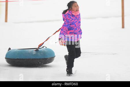 Changchun, China's Jilin Province. 15th Feb, 2019. A girl plays in the snow at Nanhu park in Changchun, northeast China's Jilin Province, Feb. 15, 2019. Credit: Lin Hong/Xinhua/Alamy Live News - Stock Photo