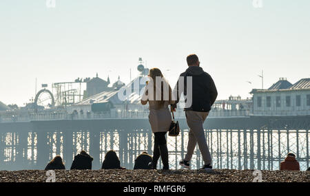 Brighton, UK. 15th Feb, 2019. Visitors enjoy the warm sunny weather on Brighton beach today as the forecast is for more of the same over the weekend Credit: Simon Dack/Alamy Live News - Stock Photo