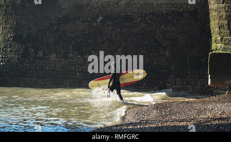 Brighton, UK. 15th Feb, 2019. A surfer enters the sea off Brighton beach today on a warm sunny day as the forecast is for more of the same over the weekend Credit: Simon Dack/Alamy Live News - Stock Photo