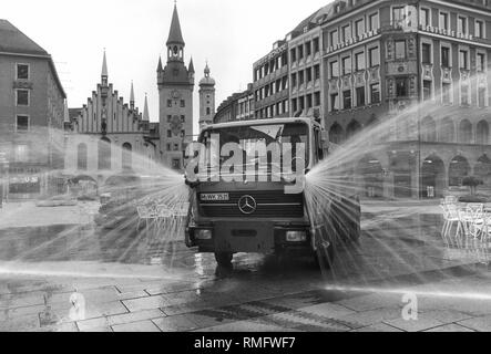 A cleaning trolley of the building directorate cleans the Munich Marienplatz with pressurized water jets every morning at 7 o'clock. In the background, the Old Town Hall as well as the tower of the Holy Spirit Church. - Stock Photo