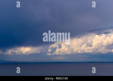 Dark storm clouds gather over the ocean while patches of sunlight shine through. False Bay, Cape Town, South Africa. - Stock Photo