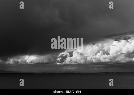 Black and white image of storm clouds of the ocean. - Stock Photo