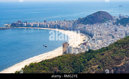 Majestic drone view of distant helicopter flying over sandy beach and modern coastal city in Brazil - Stock Photo