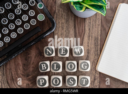 words NEW BLOG POST on wooden blocks on table with note pad, potted plant and vintage typewriter - Stock Photo