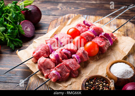 Raw shish kebab skewers  with tomatoes - Stock Photo