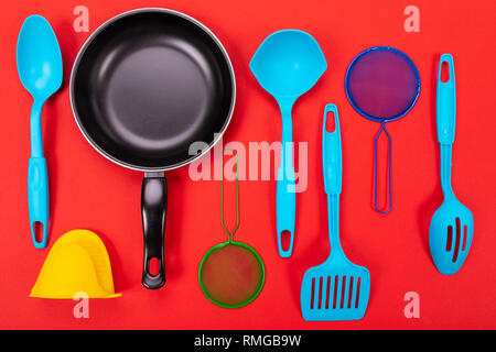 Frying pan with kitchen utensils isolated on red background - Stock Photo