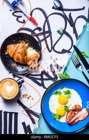 American breakfast with sunny side up eggs, bacon, coffee and croissant. Top view. The Art of food. - Stock Photo