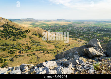 Viewpoint over a flat valley with rural villages surrounded by farmlands and arid hills. Sunset view from a peak in Macin mountains, Romania. - Stock Photo