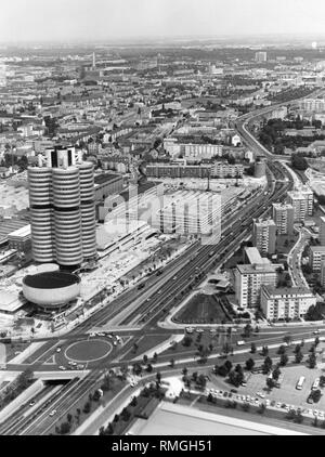 The northern Mittlerer Ring during the last finishing works. The Petuelring in the north of Munich was expanded in the early 1970s in the course of the Summer Olympic Games. In the background is the new characteristic BMW-Vierzylinder (BMW four-cylinder) in which is located the head office of the car manufacturer. The prestige building was inaugurated in the spring of 1973. - Stock Photo