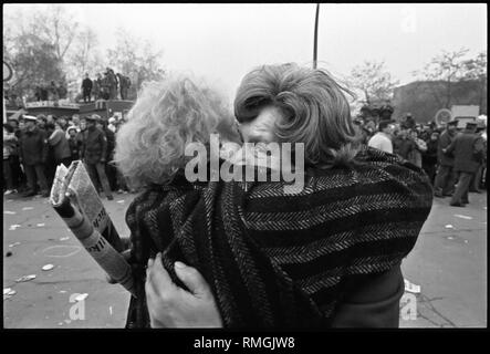 Opening of the Berlin Wall at Potsdamer Platz. Two Berlin women fall hug each other with joy at the opening of the border. - Stock Photo