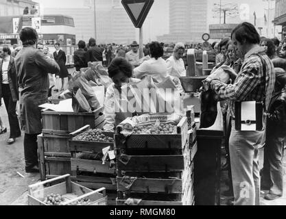 A saleswoman puts grapes into a bag at a fruit stand on Alexanderplatz in East Berlin for customers. In the background on the right the Urania World Clock. Undated photo. - Stock Photo