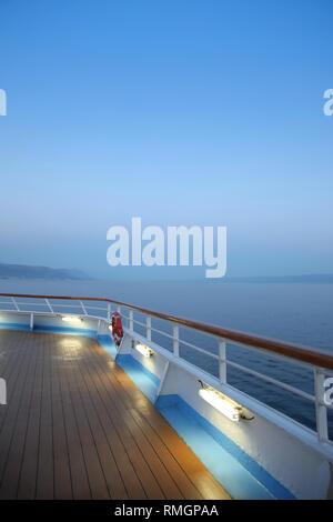 Twlight over a cruise ship deck; a relaxing way to travel, sailing across the calm ocean. - Stock Photo