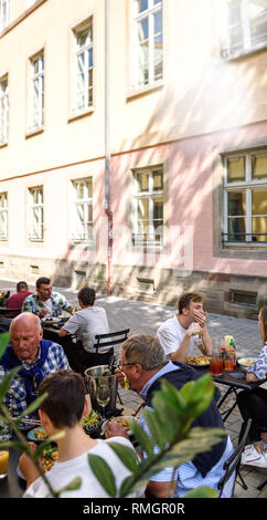 STRASBOURG, FRANCE - SEP 15, 2018: Group of happy customers enjoying food on Place des Orphelins central square in Strasbourg with East Canteen restaurant serving food to outdoor terrace customers tilt-shift lens - Stock Photo