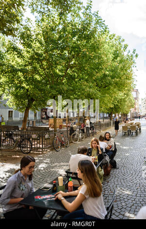 STRASBOURG, FRANCE - SEP 15, 2018: Happy customers enjoying food on Place des Orphelins central square in Strasbourg with East Canteen restaurant serving food to outdoor terrace customers tilt-shift lens - Stock Photo