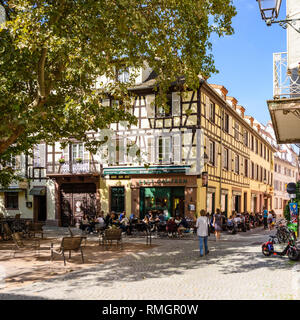 STRASBOURG, FRANCE - SEP 15, 2018: Alsatian houses in Place des Orphelins central square in Strasbourg with East Canteen restaurant serving food to outdoor terrace customers tilt-shift lens - Stock Photo