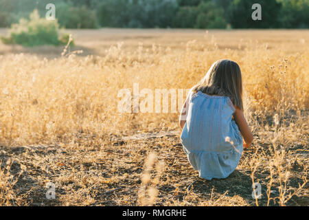 Young blonde girl crouched on the ground playing with the plants wearing a dress in the sunset field - Stock Photo