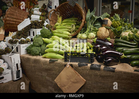 Green groceries including courgettes, aubergines, asparagus, red peppers and broccoli on sale at a vegetables stall in a local farmer market. - Stock Photo