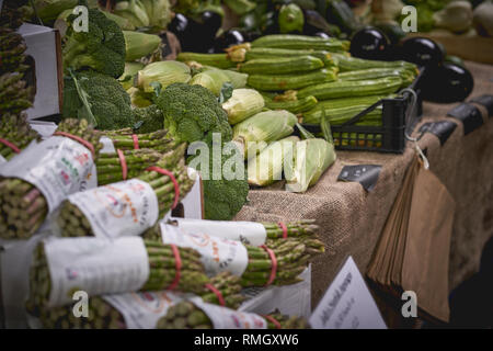 London, UK - June, 2018. Green groceries including courgettes, aubergines, asparagus, peppers and broccoli on sale at a vegetables stall in a market. - Stock Photo