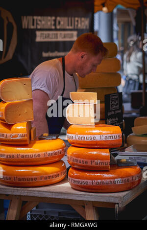 London, UK - June, 2018. Dutch Gouda cheese on sale at a stall in Borough Market, one of the oldest and largest food market in London. - Stock Photo