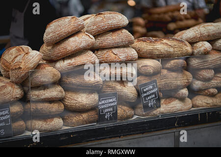 Stacks of organic brown and white sourdough bread loaves on sale in a local farmer market. Landscape format. - Stock Photo