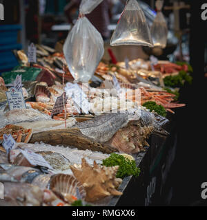 London, UK - June, 2018. Variety of fishes and shellfishes on sale at a fishmonger stall in Borough market. - Stock Photo