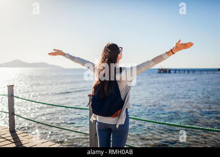 Young female tourist with backpack admiring landscape of Red sea and Tiran island on pier. Traveling concept. Summer vacation - Stock Photo