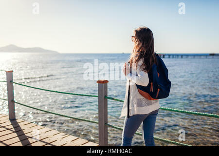 Young female tourist with backpack admiring landscape of Red sea and Tiran island walking on pier. Traveling concept. Summer vacation - Stock Photo