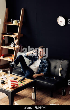 handsome man sitting on sofa and drinking beer at messy apartment - Stock Photo