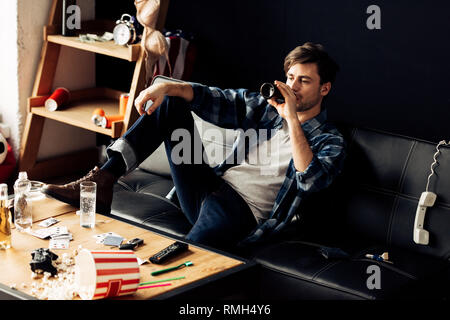 drunk man sitting on sofa and drinking beer at messy apartment - Stock Photo