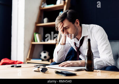 man in suit sitting near bottle and having headache after party - Stock Photo