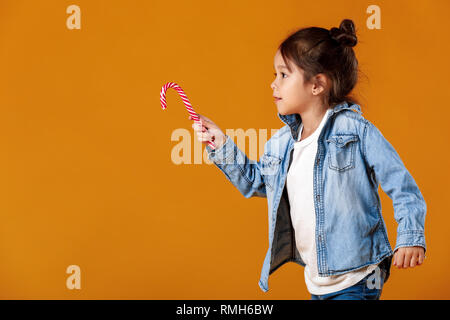 happy little girl in jeans clothes holding lollipop on orange background. child with Xmas candy cane