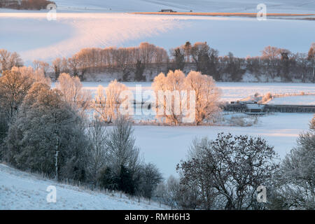 Snow covered winter landscape at sunrise in Avebury, Wiltshire, England - Stock Photo
