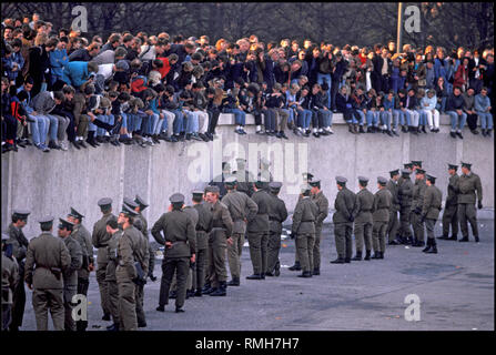 Berlin, November 10, 1989: Thousands of Berliners are gathering on the Berlin Wall at the Brandenburg Gate. GDR border guards prevent people from entering the restricted area. - Stock Photo