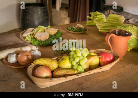 Closeup of various fruits and vegetables lying on an old wooden table - Stock Photo