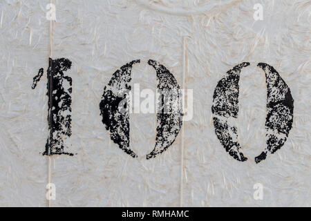 one hundred, number one hundred painted stencil on white backdrop - Stock Photo