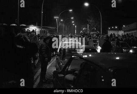 Germany, Berlin, November 9, 1989: Opening of the Berlin Wall on November 9, 1989, at the border crossing Bornholmer Strasse / Boesbruecke. Citizens of the GDR travel by car or walk to West Berlin. Traffic jam in front of the border crossing. - Stock Photo
