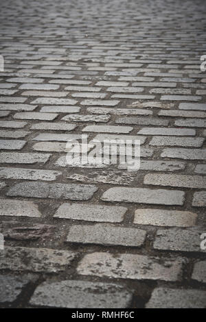 A cobblestone paved road. Portrait format. - Stock Photo